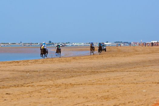SANLUCAR DE BARRAMEDA, CADIZ, SPAIN - AUGUST 10: Unidentified rider at the start of race horses on Sanlucar de Barrameda beach on August 10, 2011 in Sanlucar de Barrameda, Cadiz, Spain.