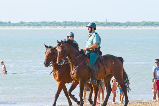 SANLUCAR DE BARRAMEDA, CADIZ, SPAIN - AUGUST 10: Security forces patrol the beach on horses races of the beach of Sanlucar de Barrameda on August 10, 2011 in Sanlucar de Barrameda, Cadiz, Spain.
