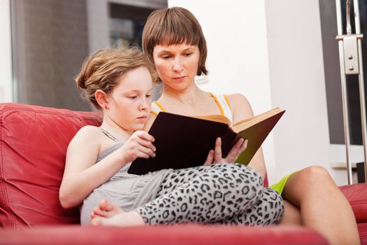 Mother and teenager daughter sitting on sofa together and reading an old book
