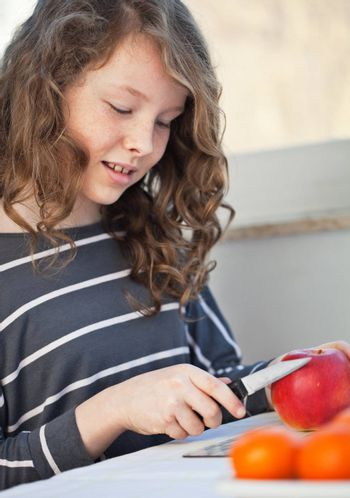 Cute teen girl cutting in the kitchen and cutting an apple with a knife