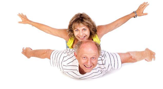 Senior couple having fun, indoors. Isolated against white..