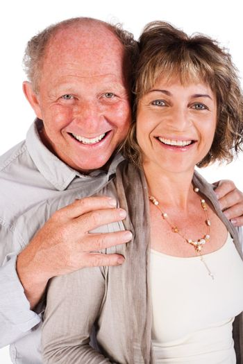 Attractive old couple posing as man hugs his wife from behind, isolated on white background.