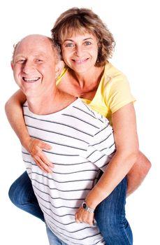 Senior man giving woman piggyback ride, indoors..