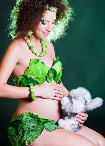 beautiful pregnant young woman dressed in cabbage