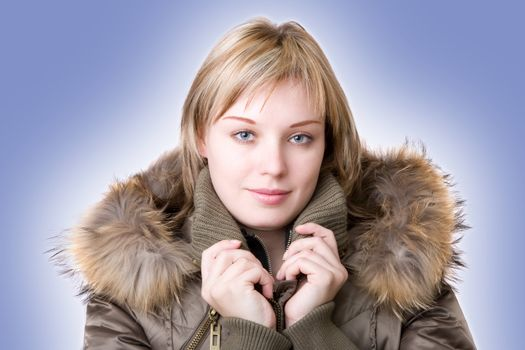 young girl in a jacket with a fur collar on a light blue background