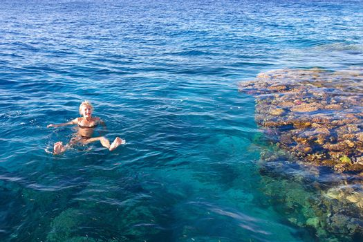 The girl carefree swim in the sea near to corals, pleasure by the sea
