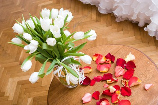 Vase with white tulips on a wooden little table and petals of a red tulip beside
