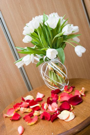 white tulips in vase and petales ot red tulips on the table