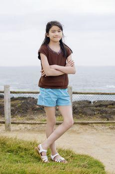 Little nine year old girl posing arms crossed by ocean