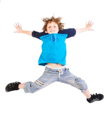 Attractive young kid jumping high, indoors.