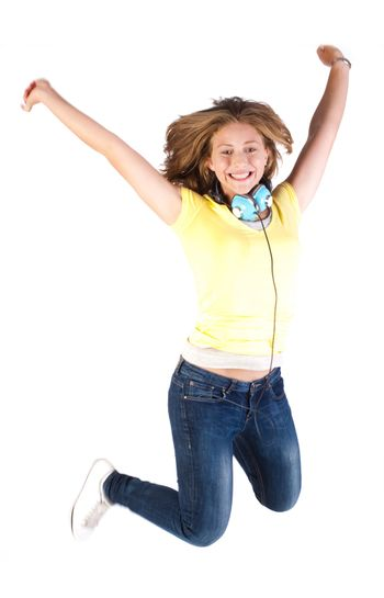 Girl jumping high with headphones around her neck, indoors.