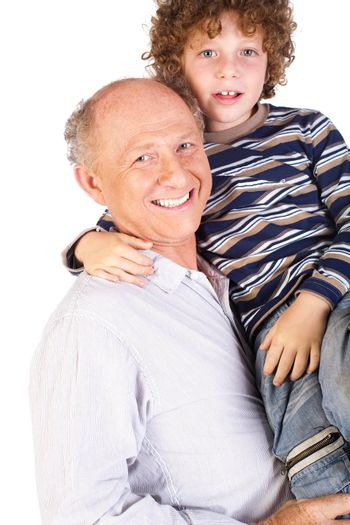 Grandfather and grandson indoors smiling.