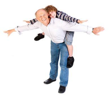 Grandfather giving grandson piggy-back against white background.