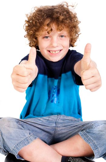 Young kid smailing at camera and showing double thumbs up isolated on white.