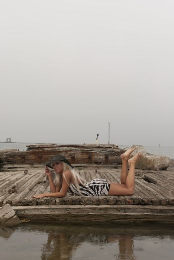 girl in a hat lying on a broken ship at sea