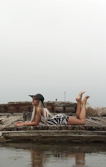 girl in a hat sitting on a broken ship at sea