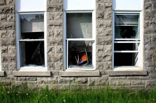 Chair thrown in window by vandals on historic building