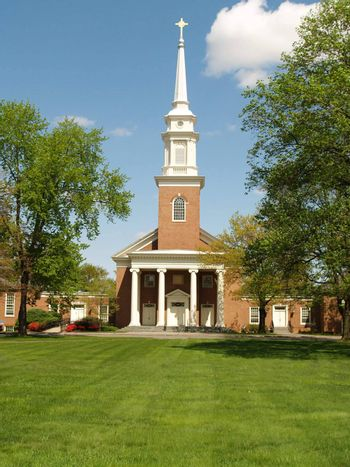 a front view of a big red church in the country.  In the front of the church is a green lawn and a blue sky in the background.