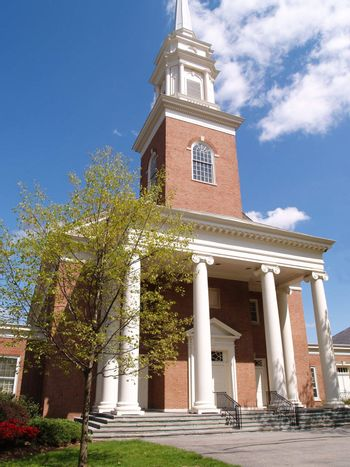 A front view of a big red brick church with large white columns.