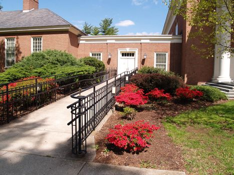a sidewalk leading to a red brick building.  By the sidewalk are landscaping bushes and flowers.