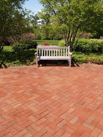 an empty wooden bench by a brick patio and garden