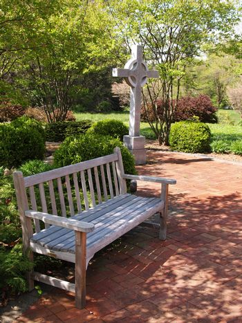 an empty wood bench by a red brick patio and a cross