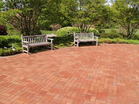 two empty wood benches by a red brick patio in a garden