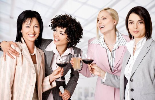Team of four happy businesswomen smiling and celebrating