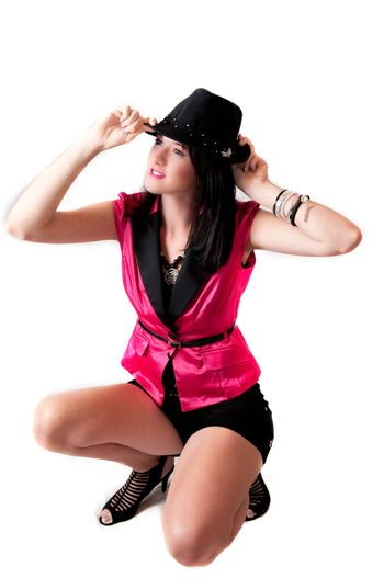 Beautiful sexy brunette model with blue eyes in sexy pink jacket and black hat kneeling down