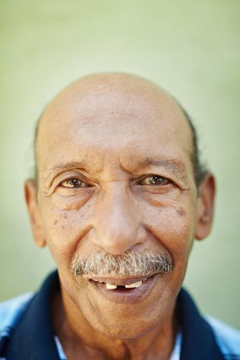 portrait of senior hispanic man with dental problems looking at camera against green wall. Vertical shape
