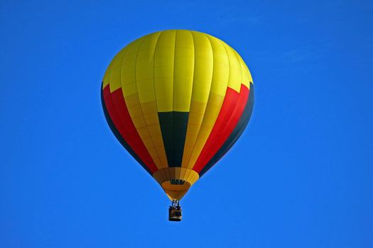 Hot air balloon on blue background with red black and yellow highlights.