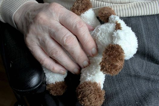 Elderly woman's hand holding a small doll