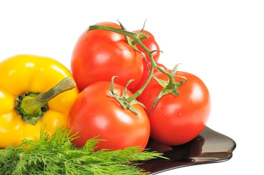 Vegetables - Tomatoes, peppers on a plate with dill. Isolated on white.
