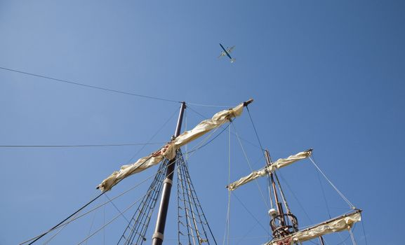 Jet pane and an old sailing ship against a summer blue sky - Croatia.