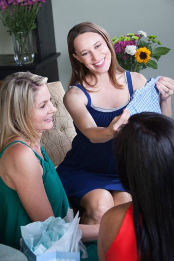 Smiling pregnant woman with gift at baby shower