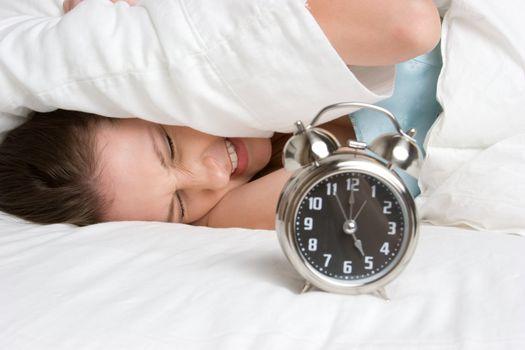 Sleeping woman waking alarm clock