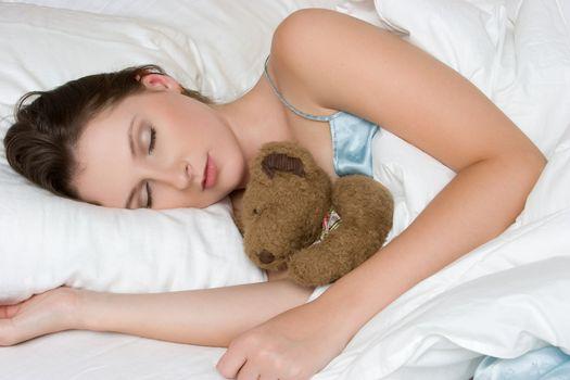 Woman sleeping with teddy bear