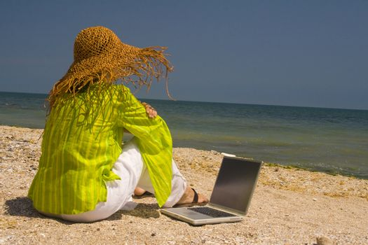 Woman in hat sitting on beach working on laptop