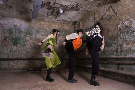 Aggressive girls of goth in a gloomy dirty cellar