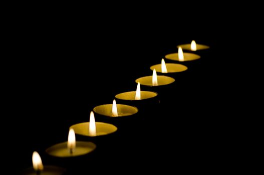 Row of candles in darkness with shallow depth of field and copy space