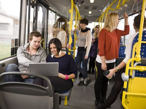 Couple with computer going by bus