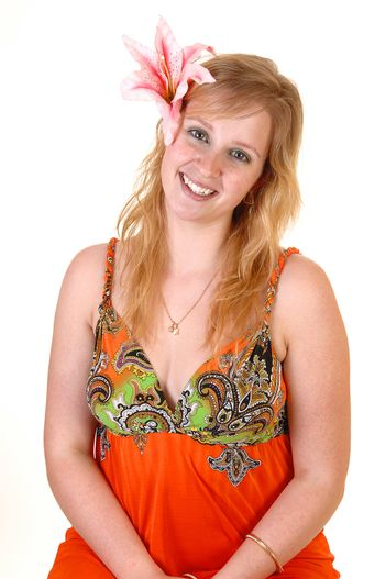 An gorgeous teenager girl in a colourful orange dress and a lily in her hair standing in the studio with a pretty smile, for white background.