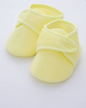 babies shoes in a yellow towelling fabric
