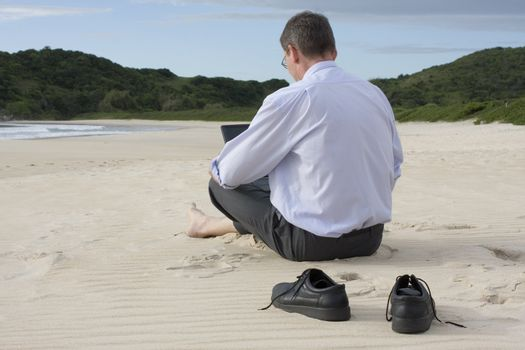 Businessman working with his laptop while sitting barefoot on the beach.