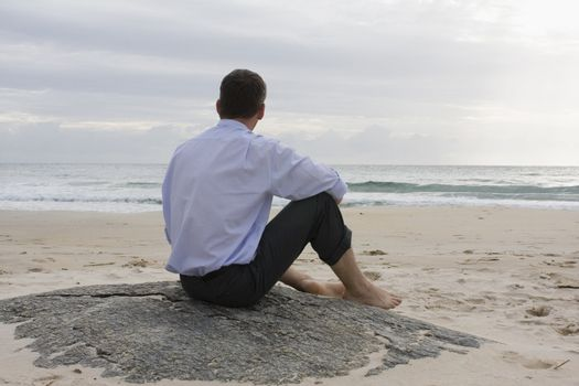 Businessman contemplating the sea while sitting barefoot on a rock on the beach