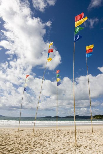 Flagpoles with colorful flags on the beach against blue sky with white clouds
