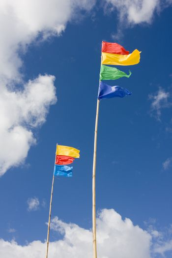 Colorful flags waving in the wind with blue sky and white clouds in the background