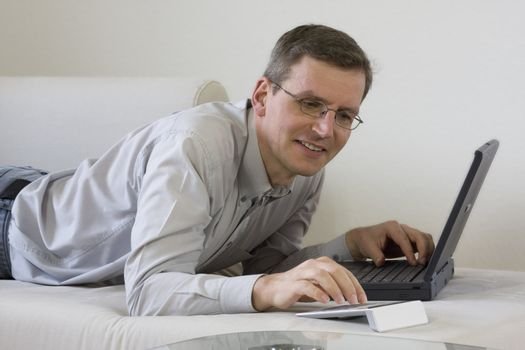 Man lying on a coach with laptop computer and calculator