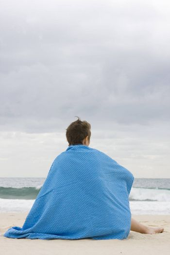 woman with blue blanket sitting on a beach