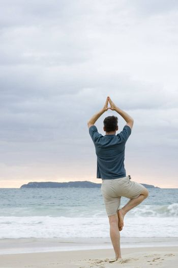 Man doing yoga on a beach at sunrise